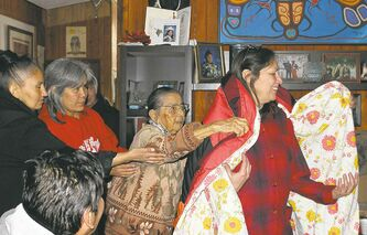 Rose Cobiness (left) of Buffalo Point, Chief Patricia Big George of Big Island Ontario and Florence Cobiness Kakaygeesick of Buffalo Point take part in the ceremonial draping of newly elected chief Andrea Camp-Colette at Buffalo Point First Nation.