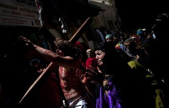 A Christian pilgrim dressed as Jesus Christ carries a cross during a reenactment of the crucifixion during a Good Friday procession in Jerusalem's Old City, Friday. Less than two per cent of the population of Israel and the Palestinian territories is Christian, mostly split between Catholicism and Orthodox streams of Christianity. Christians in the West Bank wanting to attend services in Jerusalem must obtain permission from Israeli authorities. Israel's Tourism Ministry said it expects some 150,000 visitors in Israel during Easter week and the Jewish festival of Passover, which coincide this year.