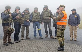 U.N. inspectors of the Organization for the Prohibition of Chemical Weapons,OPCW, discuss after a training session in the German Armed Forces training center in Wildflecken, Germany, Wednesday, Oct. 16, 2013. 24 U.N. experts from 17 different countries are attending a five-day training before starting their mission to Syria. (AP Photo/Jens Meyer)