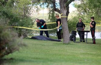 Police officers investigate after the body of a man was found by a retention pond in northwest Winnipeg Friday morning.