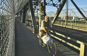 The sun casts a warm glow on a cyclist as he makes his way over the Arlington Street bridge.