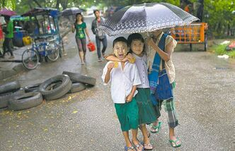 Children wearing school uniforms eat a snack as they walk to school in the rain in Yangon, Myanmar, Friday.