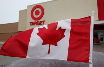 A Canada flag flies on a customer's car parked in front of the new Target store in Guelph, Ont. on Tuesday March 5, 2013. Target's expansion into Canada is continuing in big way over the next two weeks as the American retailer opens 21 new stores in Ontario. THE CANADIAN PRESS/Dave Chidley