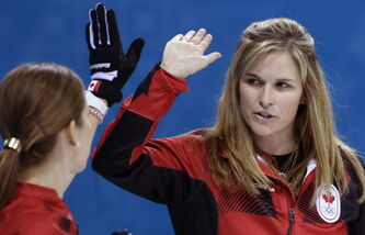 Jennifer Jones congratulates Kaitlyn Lawes after her throw during women's curling competition against Japan.