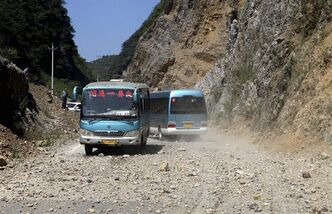 In this photo provided by China's Xinhua News Agency, buses encoutner the rockfall triggered by an earthquake in Yiliang County, southwest China's Yunnan Province, Friday, Sept. 7, 2012. A series of earthquakes collapsed houses and triggered landslides in a remote mountainous part of southwestern China on Friday, killing at least 50 people with the toll expected to rise. Damage was preventing rescuers from reaching some outlying areas, and communications were disrupted. (AP Photo/Xinhua, Zhang Guangyu) NO SALES