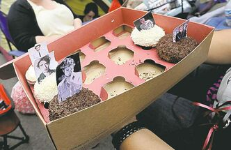 Twilght fans look at cupcakes with Robert Pattinson's photo as they wait in a movie line in Los Angeles.