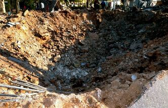 In this photo released by the Syrian official news agency SANA, Syrian people gather in front of a crater caused by an explosion hit a university in Aleppo, Syria, Tuesday, Jan. 15, 2013. Two explosions struck the main university in the northern Syrian city of Aleppo on Tuesday, causing an unknown number of casualties, state media and anti-government activists said. There were conflicting reports as to what caused the blast at Aleppo University, which was in session Tuesday. (AP Photo/SANA)