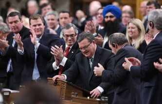 Minister of Finance Jim Flaherty is applauded as he arrives to table the budget in the House of Commons on Parliament Hill in Ottawa on Tuesday, February 11, 2014.