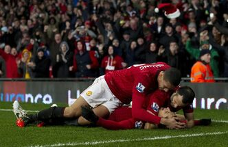 Manchester United's Javier Hernandez, bottom, celebrates with teammates Ryan Giggs and Chris Smalling after scoring against Newcastle during their English Premier League soccer match at Old Trafford Stadium, Manchester, England, Wednesday, Dec. 26, 2012. (AP Photo/Jon Super)
