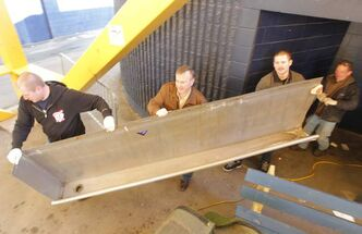 Leigh Young, second from left, got some help moving the trough. Sons Cole, left, and Chad, second from right, assisted as did uncle Jim Nielsen, right.