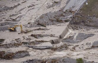 Crews work on the washed out Trans-Canada Highway during heavy flooding in Canmore, Alta. Friday. Soldiers at CFB Shilo are on standby in case they are needed in the province.