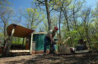 Drew Richardson splits wood for the fire outside one of the yurts set among  the oaks at the Kiche Manitou campground in Spruce Woods Provincial Park.
