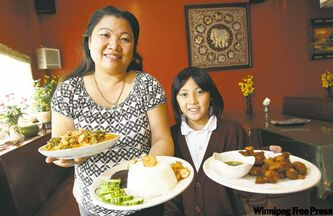 Lao Thai's owner, Khamlaa Boonthajit, with her grand- daughter, Sommerlyn Boonthajit, 9. They hold, from left, gang-pet red curry, shrimp Thai fry and chicken skewers.