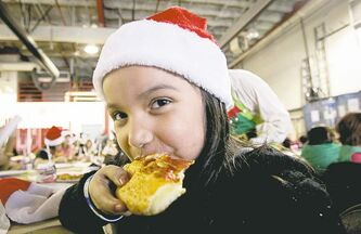 Rinelle Constant, 8, from Mulvey School, enjoys her pizza while waiting for Santa to arrive.