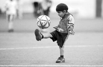 A turban-wearing boy practises soccer in Quebec.