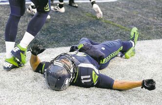 Seattle Seahawks wide receiver Percy Harvin lies on the ground after being injured during the second quarter of an NFC divisional playoff NFL football game against the New Orleans Saints in Seattle, Saturday, Jan. 11, 2014. (AP Photo/Ted S. Warren)