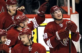 Phoenix Coyotes' Shane Doan (19) watches the video replay as teammate Mikkel Boedker (89), of Denmark, pats him on the helmet after Doan's hat trick performance against the New York Islanders after an NHL hockey game on Saturday, Jan. 7, 2012, in Glendale, Ariz. The thought has at least crossed Shane Doan's mind. With the Phoenix Coyotes ownership situation still in limbo and unrestricted free agency staring him in the face, the veteran forward could be playing out his final NHL season. THE CANADIAN PRESS/AP-Ross D. Franklin