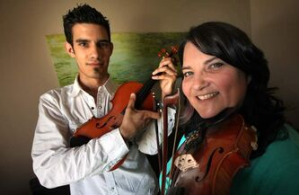 Patti Lamoureux and son Alex with their fiddles. Patti is leading the local staging of World Fiddle Day on Saturday.