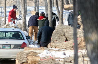 Workers and Brandon Police Service members erect a tent near the banks of the Assiniboine River in Queen Elizabeth Park on Wednesday afternoon. City police confirm that they're investigating after human remains were found on Tuesday evening.