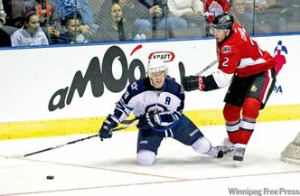 Jets forward Brian Little tries to set up a play from his knees while Sens defenceman Jared Cowen makes a move on the puck.