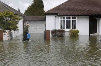 A man wades through a flooded street, in Egham, England, Wednesday, Feb. 12, 2014. The country is dealing with its worst flooding in nearly 250 years.