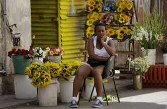 A flower vendor waits for clients near the Virgin of Charity of Cobre Catholic church in Havana, Cuba, Thursday March 15, 2012. A group of Cuban dissidents who have occupied the church for two days are no longer demanding an audience with Pope Benedict XVI when he visits this month, but vowed Thursday to continue their protest. The dissidents say they are now asking the pontiff to mediate a list of their grievances with the Cuban government. (AP Photo/Franklin Reyes)