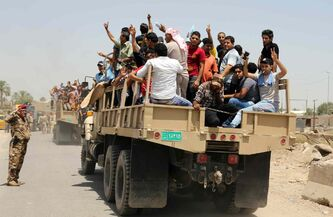 In this June 14, 2014 photo, Iraqi men fill a military truck to join the Iraqi army at the main recruiting center in Baghdad, Iraq, after authorities urged Iraqis to help battle insurgents.