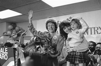 FILE - In this Sept. 10, 1984 file photo, Joan Mondale, wife of the Democratic presidential candidate Walter Mondale, center, waves to the campaign workers gathered at the Illinois headquarters for the Mondale-Ferraro election effort, in Chicago. Mondale is flanked by campaign worker Julie Grace, holdings Lauren Jascula, who also wanted to show her support. Joan Mondale, who burnished a reputation as