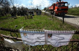 Death notices of Milos and Ljubina Jesic, victims of a shooting that left 13 people dead are seen on the cemetery fence in the village of Velika Ivanca, Serbia, Thursday, April 11, 2013. The suspect in fatal shootings of 13 in Serbia, Ljubisa Bogdanovic, has died, hospital officials said. The 60-year-old man gunned down 13 people, including a baby, in a house-to-house rampage in a quiet village on Tuesday before trying to kill himself and his wife. (AP Photo/Darko Vojinovic)