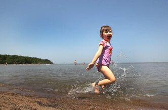 Ella Bergen, 4, cools off in Lake Winnipeg at Grand Beach on Wednesday as temperatures topped out in the low 30 C range.