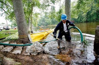 Raul Vervuzco of Eagle Services (right) uses a suction hose to clean oil from atop the Kalamazoo River July 28 in a containment area in Au­gusta, Mich. Enbridge operates the pipeline that dumped approximately 3.8 million litres of oil into a southern Michigan river.