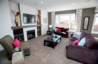 The family room has a gas fireplace and benefits from its high ceiling and huge picture window.