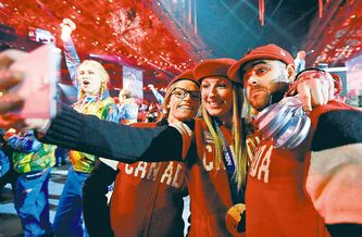 Canadian athletes take a self-portrait with a mobile phone during the closing ceremony.