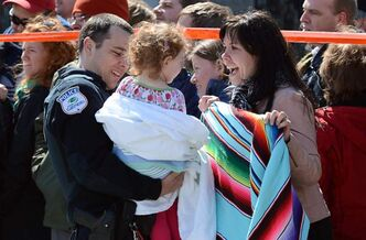 A child is is welcomed after police release children to family at the scene of a shooting in Gatineau on Friday.