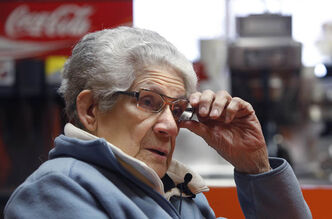 Mary Kelekis, owner of Kelekis Restaurant on Main St., sits down prior to opening the doors to let in the crowd lined up outside for the second last day of operation.