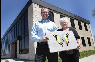 Michel Morin and Manitoba Master Gardener Association's Leona Schroeder show a stained glass butterfly design on a patio block for the butterfly garden.