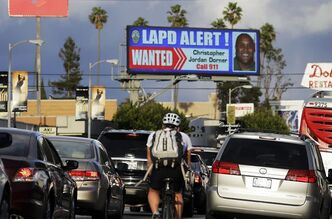 "In this Feb. 8, 2013 photo, commuters on Santa Monica Boulevard on the Westside of Los Angeles see a digital billboard displaying a large ""wanted"" poster for former Los Angeles police Officer Christopher Dorner. Dorner is suspected in a spree of violence as part of a vendetta against law enforcement after being fired by the department. He is also a suspect in the shooting deaths of a former LAPD captain's daughter and her fiance, and two other shootings that left an officer dead and two others wounded. Dorner's alleged killing spree hasn't just terrorized a large section of the country _ it has captured people's imagination and attention. (AP Photo/Reed Saxon)"