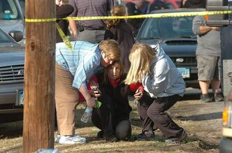 People are comforted near Sandy Hook Elementary School on Friday.