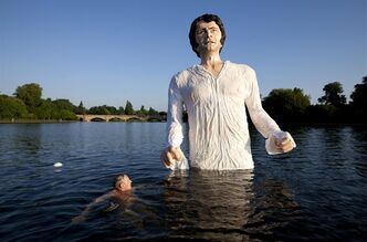 A swimmer approaches a statue meant to depict actor Colin Firth performing as Mr. Darcy, a character in Jane Austen's novel