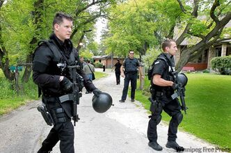 Winnipeg police tactical officers leave the Angels clubhouse on Scotia Street after the police raid.