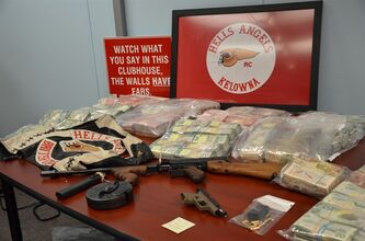 An assault rifle, handguns and nearly $4 million in cash is seen in this RCMP handout photo in Vancouver, Monday, August 27, 2012. An RCMP drug investigation that took nearly two years and involved authorities from Canada, the U.S., Panama and Mexico has resulted in charges against eight people, including some top members from the Hells Angels motorcycle gang in British Columbia. THE CANADIAN PRESS/HO - RCMP