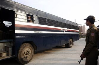 A police officer stands guard next to a police van believed to be carrying the five men accused in a gang rape as they leave the district court in New Delhi, India, Monday, Jan. 14, 2013. The cases of five men charged in the fatal gang rape of a young woman on a moving New Delhi bus were expected to be shifted to a fast-track court at a hearing Monday, defense lawyers said. Five men have been charged with the Dec. 16 attack on the 23-year-old student, who died two weeks later in a Singapore hospital. (AP Photo/Tsering Topgyal)