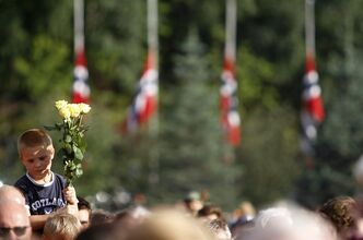 A boy holds up flowers as Norwegian flags fly at half-mast during a vigil in memory of the eight people killed in Friday's blast in Oslo and the 68 who died in the shooting at the youth camp on Utoya, in Vik, near Sundvollen, close to Utoya island, near Oslo, Norway, Tuesday, July 26, 2011. (AP Photo/Ferdinand Ostrop)
