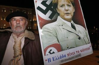 An angry Greek protester holds a poster with a picture of Angela Merkel in a Nazi uniform during demonstrations against Germany's recovery plan.