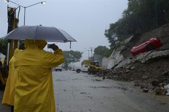 A man takes a photo with his phone as a car lies on its side after a portion of a hill collapsed due to heavy rains in the Pacific resort city of Acapulco, Mexico, Sunday, Sept. 15, 2013.Flooding and landslides unleashed by Hurricane Ingrid and Tropical Storm Manuel have claimed at least a dozen lives in Mexico and sparked the evacuations of thousands of people even before the weather systems had made landfall on the country's east and west coasts. (AP Photo/Bernandino Hernandez)