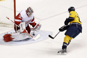 Detroit Red Wings goalie Jimmy Howard blocks a shot by Nashville Predators right wing Matt Halischuk in the second period of an NHL hockey game, Sunday, April 14, in Nashville, Tenn.