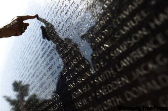 .A woman points to a name on the memorial wall in Ottawa honouring those who fought in the Battle of Hong Kong during the Second World War.