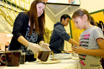 St. James Collegiate student Sierra Betker drizzles on the syrup during a pancake breakfast and I Love to Read event at Brooklands School last week.