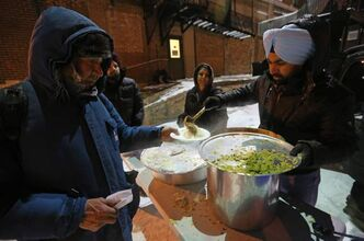 Kulwinder Sing Layal (right) a member of the Deshmesh Darbar Temple, serves food at a mobile soup kitchen behind the Siloam Mission, Saturday, in honour of Ruru Gobind Singh's birthday, which is celebrated by Sikhs around the world.