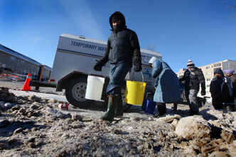 Enrique Roque carries water back to his home off Jefferson Avenue after lining up at a temporary water supply station.